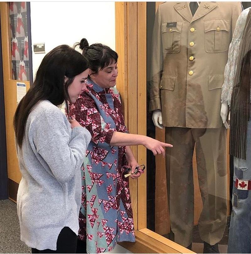 Professor Kelly Cobb showing a student the Fashion and Textile Collection